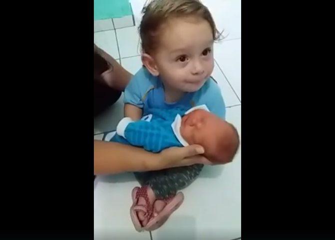 طفل يُصر على حمل رضيع وتقبيله (فيديو)