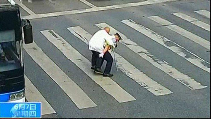شرطي يحمل مسناً على ظهره ليعبر الطريق (فيديو)