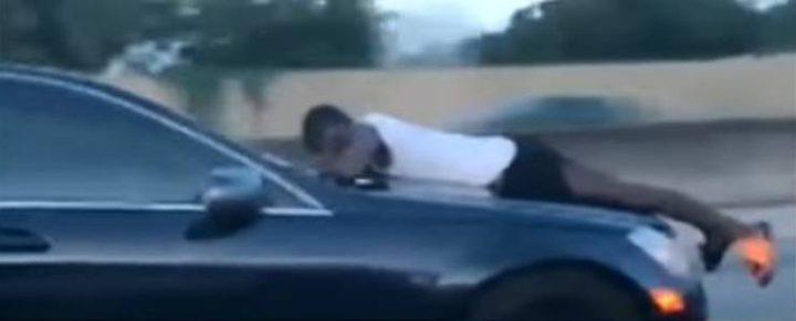 رجل يحاول منع طليقته من قيادة السيارة ويتعلق بزجاجها!