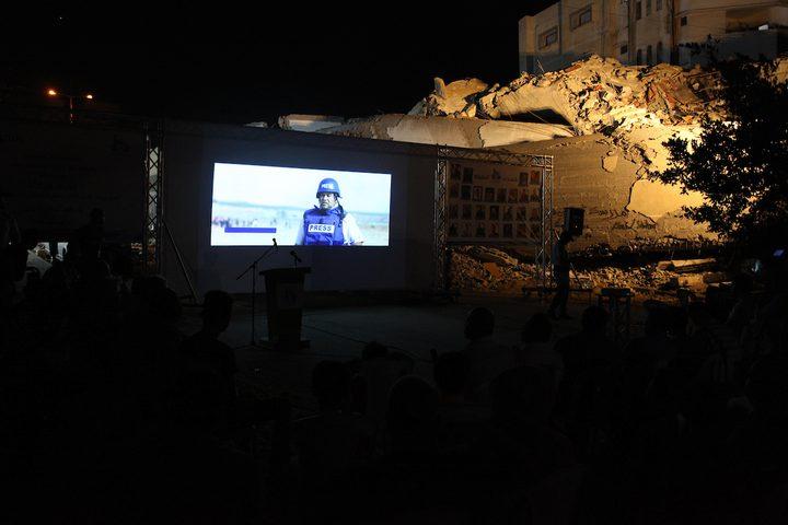 فلسطينيون يشاهدون فيلما على شاشة كبيرة بجانب أنقاض مركز سعيد المسحال الثقافي الذي دمره غارة جوية إسرائيلية على مدينة غزة في 14 أغسطس عام 2018.