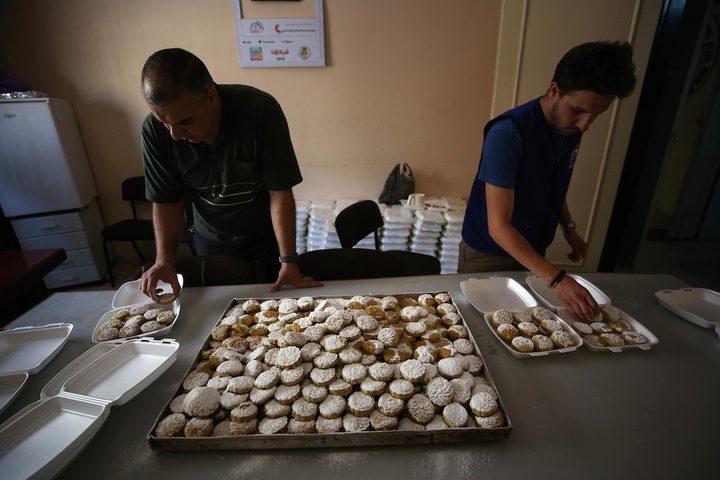 """متطوعون يقومون بإعداد """"كعك العيد"""" لتوزيعه على الأسر الفقيرة قبيل عيد الأضحى في مدينة نابلس بالضفة في 15 أغسطس عام 2018."""