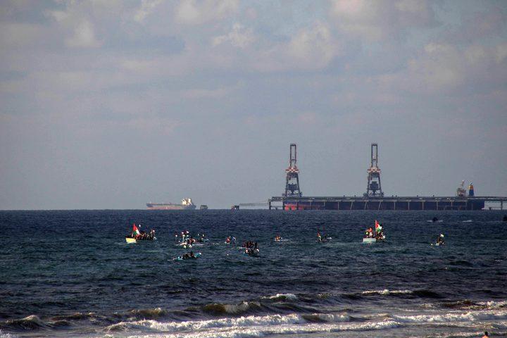 فلسطينيون يركبون قوارب صيد خلال مسيرة لكسر الحصار الإسرائيلي على قطاع غزة ، في البحر في مدينة غزة