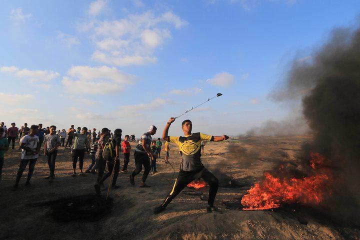 متظاهرون فلسطينيون يتجمعون خلال اشتباكات مع القوات الإسرائيلية في مسيرات العودة حيث يطالب الفلسطينيون بحق العودة إلى وطنهم على الحدود بين إسرائيل وغزة ، في خان يونس جنوب قطاع غزة