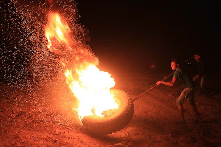 """"""" وحدة الإرباك الليلي"""" أثناء حرقهم للإطارات أمس، خلال المواجهات مع الاحتلال، والتي تهدف إلى إبقاء جنود الاحتلال في حالة استنفار دائم، مطالبين بحق العودة إلى وطنهم على الحدود بين إسرائيل وغزة، في البريج في وسط قطاع غزة."""