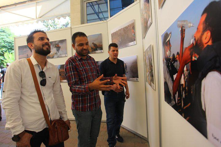 """مواطنون يحضرون معرض صور بعنوان """"صحفيون على خط النار""""، في مدينة غزة."""