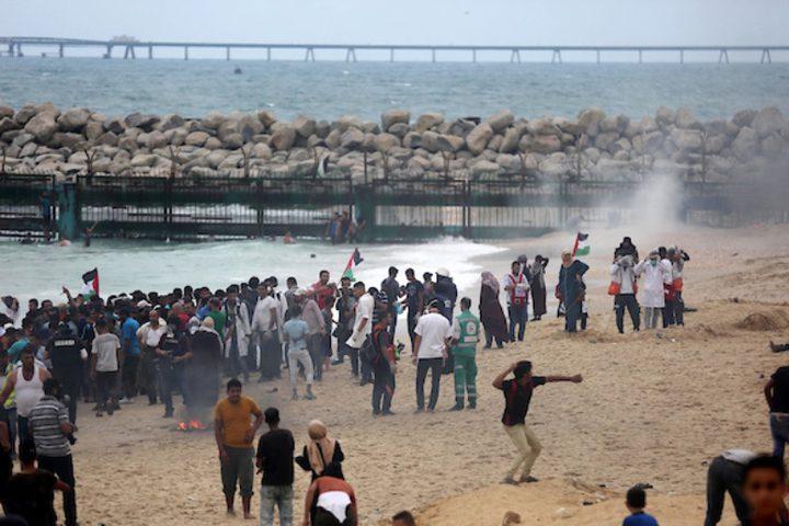 متظاهرون فلسطينيون يجتمعون خلال اشتباكات مع القوات الإسرائيلية في مظاهرة ضد الحصار الإسرائيلي على قطاع غزة ، على طول الحاجز البحري لغزة على الحدود البحرية مع إسرائيل بالقرب من كيبوتس زكيم ، شمال بيت لاهيا في شمال قطاع غزة في 1 أكتوبر 2018.