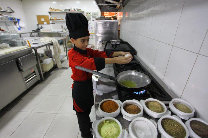 الطباخ الفلسطيني محمد أبو ندا 12عامًا يطبخ الوجبات الغربية بمطعم في مدينة غزة