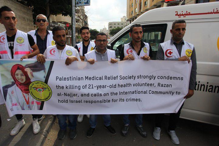 مسعفون فلسطينيون يحملون لافتات أثناء الاحتجاج للمطالبة بحمايتهم أمام مكتب الصليب الأحمر في غزة.