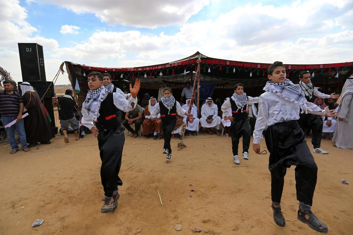 فلسطينيون يؤدون الرقص التقليدي خلال مهرجان تراثي على الحدود بين إسرائيل وغزة.