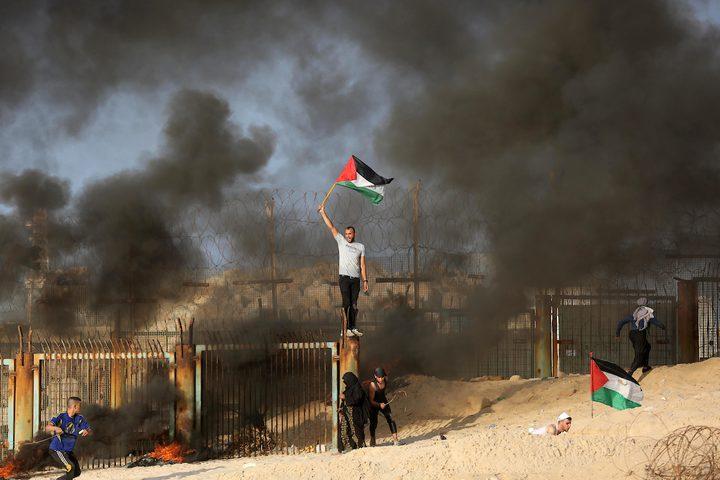متظاهرون فلسطينيون يجتمعون خلال اشتباكات مع قوات الاحتلال في مظاهرة ضد الحصار الإسرائيلي على قطاع غزة.