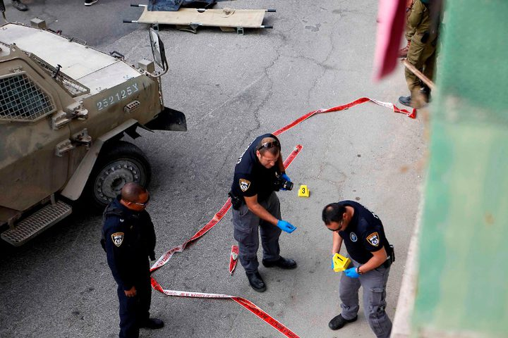 قوات الأمن الإسرائيلية تقف حول جثة فلسطيني في مسرح عملية طعن في مدينة الخليل بالضفة الغربية.