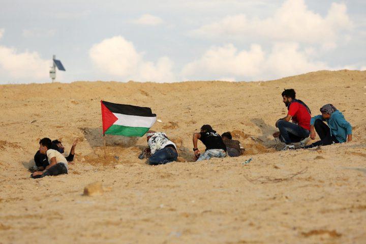 متظاهرون فلسطينيون يجتمعون خلال اشتباكات مع القوات الإسرائيلية في مظاهرة ضد الحصار الإسرائيلي على قطاع غزة، على طول الحاجز البحري لغزة على الحدود البحرية مع إسرائيل بالقرب من كيبوتس زيكيم، شمال بيت لاهيا في شمال قطاع غزة