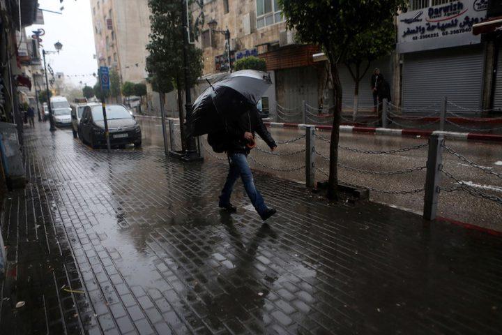 فلسطينيون يسيرون في شارع غمرته المياه في يوم ممطر في مدينة رام الله بالضفة الغربية
