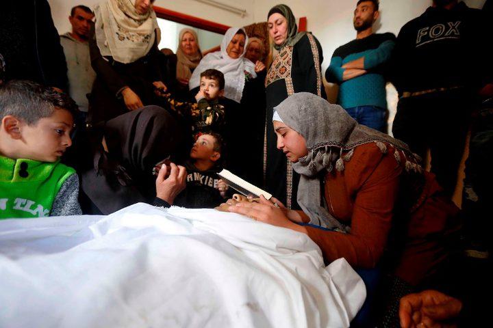 أقارب الفتى الفلسطيني عمر عواد ، 27 عاماً ، الذي قُتل برصاص القوات الإسرائيلية بعد محاولته محاولة هجوم على سيارة قرب نقطة تفتيش حدادا على جسده خلال جنازته في الخليل بالضفة الغربية المحتلة