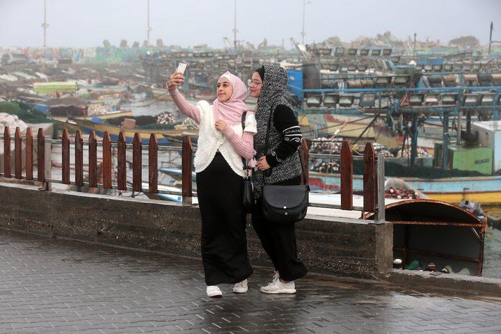 فتيات فلسطينيات يطرحن صورة ذاتية في ميناء غزة البحري في يوم ممطر في مدينة غزة في 20 ديسمبر ، 2018