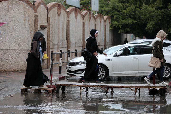 فلسطينيون يسيرون في شارع غمرته المياه في يوم ممطر في مدينة غزة في 20 ديسمبر عام 2018.