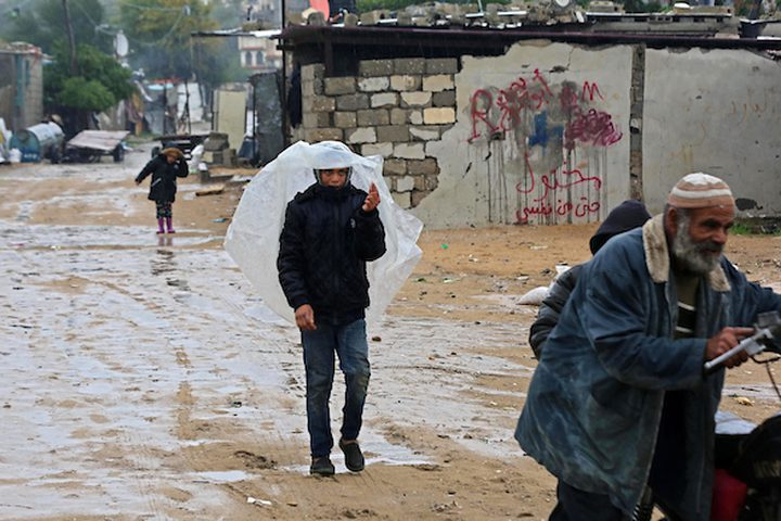 فلسطينيون يسيرون في الشارع في يوم ممطر في مخيم نهر البارد للاجئين في خان يونس جنوب قطاع غزة في 30 كانون الأول / ديسمبر 2018.
