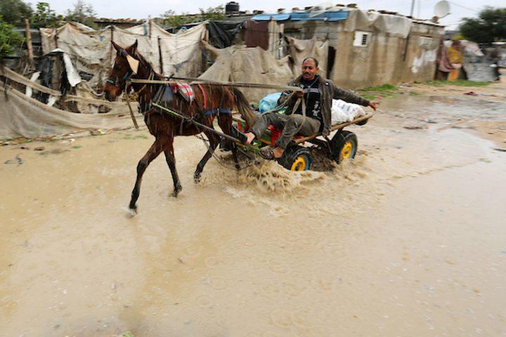 رجل فلسطيني يركب عربة خيل في يوم ممطر في مخيم نهر البارد للاجئين في خان يونس جنوب قطاع غزة في 30 كانون الأول / ديسمبر ، 2018.