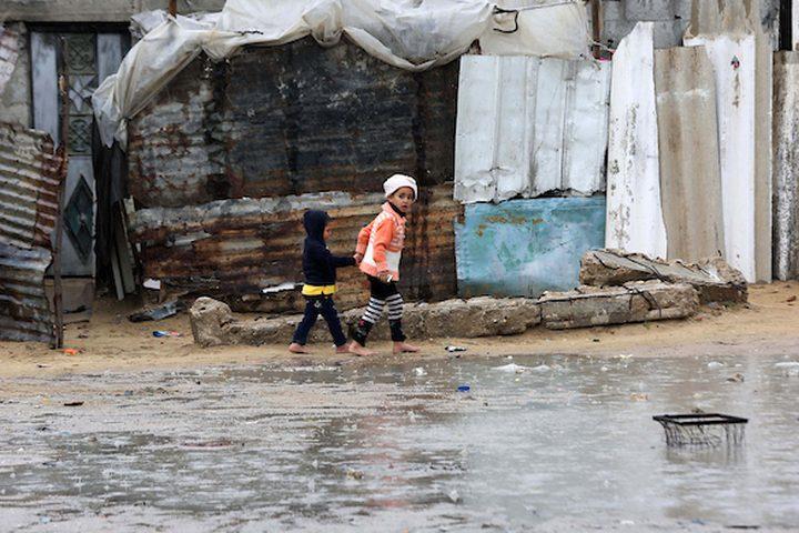 أطفال فلسطينيون يلعبون خارج مسكن عائلاتهم في يوم ممطر في مخيم نهر البارد للاجئين في خان يونس جنوب قطاع غزة في 30 كانون الأول / ديسمبر 2018