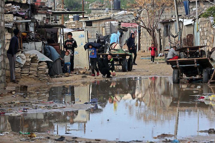 فلسطينيون يقفون في الشارع في يوم ممطر في مخيم نهر البارد للاجئين في خان يونس جنوب قطاع غزة في 30 كانون الأول / ديسمبر ، 2018.