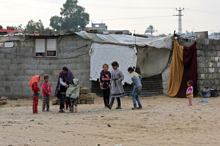 أطفال فلسطينيون يلعبون خارج مسكن عائلاتهم في يوم ممطر في مخيم نهر البارد للاجئين في خان يونس جنوب قطاع غزة في 30 كانون الأول / ديسمبر 2018.