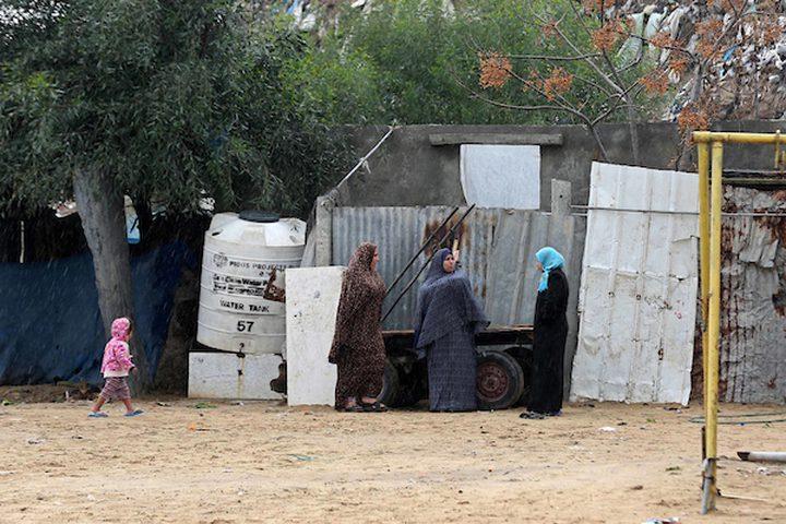 نساء فلسطينيات يقفن في الشارع في يوم ممطر في مخيم نهر البارد للاجئين في خان يونس جنوب قطاع غزة في 30 كانون الأول / ديسمبر 2018.