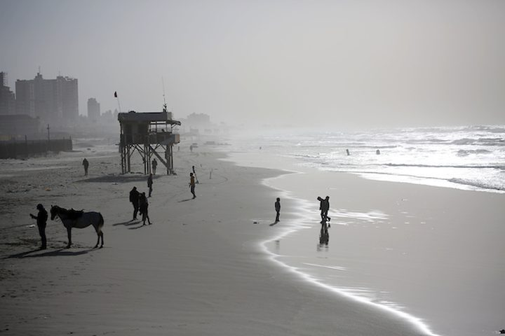فلسطينيون يسيرون على شاطئ مدينة غزة في يوم عاصف ، في 7 يناير ، 2019.