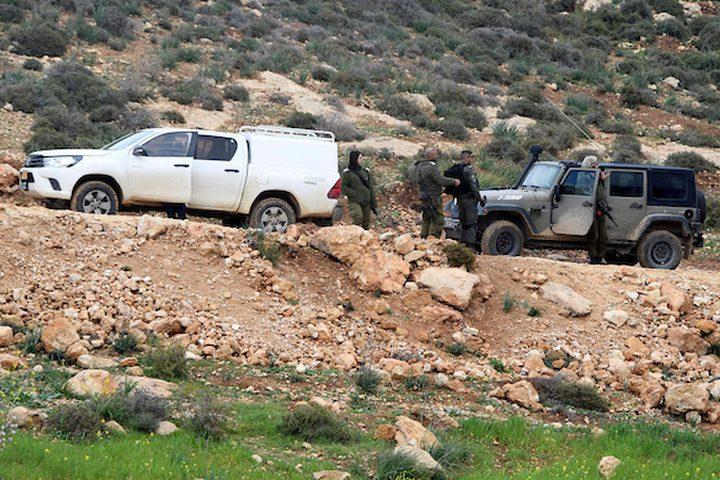 قوات الأمن الإسرائيلية تقف حارسة عندما تدمر جرافة تابعة للجيش الإسرائيلي تدمير الطريق في قرية يطا جنوب مدينة الخليل بالضفة الغربية في 11 فبراير / شباط 2019.