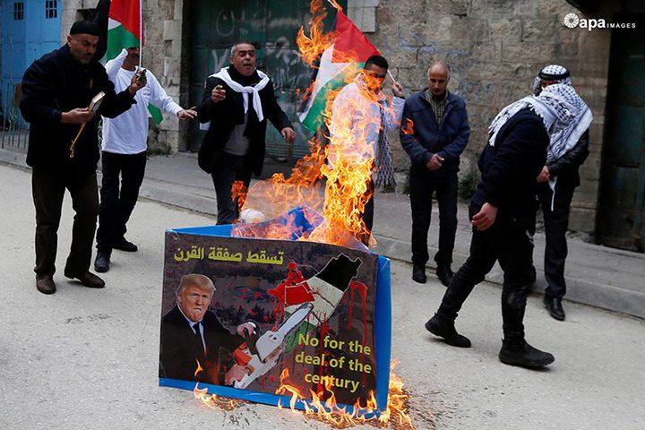 مواطنون يحرقون صور للرئيس الأمريكي دونالد ترامب خلال مظاهرة ضد صفقة القرن في مدينة الخليل