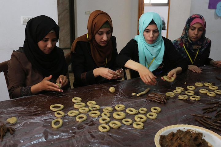 مجموعة من الفتيات في مخيم المغازي وسط القطاع ،يعددن الكعك على الطريقة التقليدية ,,لبيعه للمواطنين في غزة قبل عيد الفطر