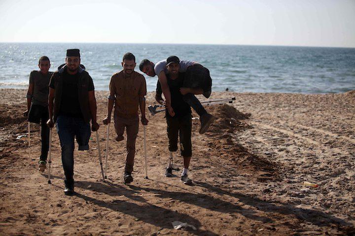 شبان فلسطينيون جرحى ،  فقدوا أرجلهم خلال الاشتباكات مع القوات الإسرائيلية ، يقفون أمام قرعة رملية خلال مظاهرة تدعو لمقاطعة شركة بوما الرياضية ، على شاطئ مدينة غزة