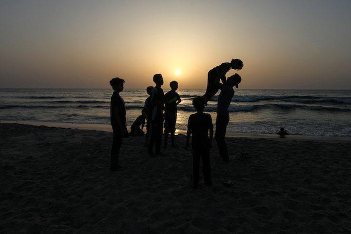 شاب فلسطيني يلعب الباركور على شاطئ البحر الأبيض المتوسط أثناء غروب الشمس ، في مدينة غزة.