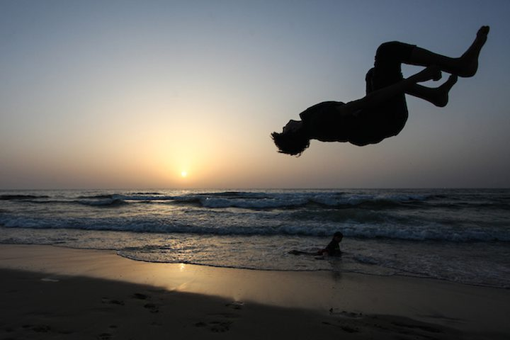 شاب فلسطيني يلعب الباركور على شاطئ البحر الأبيض المتوسط أثناء غروب الشمس ، في مدينة غزة .