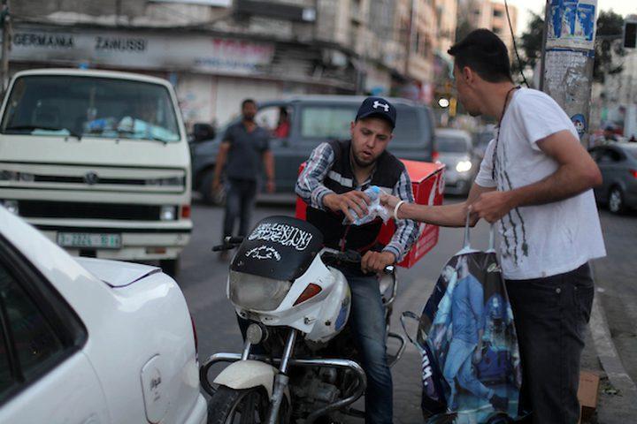 رجل مسيحي فلسطيني يوزع التمر والماء على المسلمين ، قبل الإفطار مباشرة في شهر رمضان المبارك ، في مدينة غزة