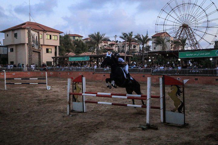 متسابقون فلسطينيون يقفزون مع أحصنتهم خلال مسابقة الفروسية المحلية ، في شمال مدينة غزة .