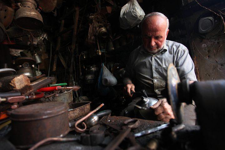رجل فلسطيني ، أبو هاني المصعبي ، 68 عاماً ، يعمل على تصنيع وصيانة أدوات تقليدية من الكيروسين وأواني الطهي في متجره في مدينة غزة.
