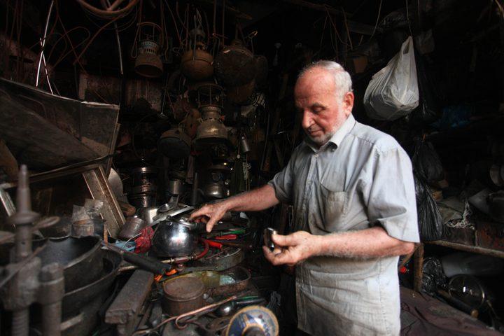رجل فلسطيني ، أبو هاني المصعبي ، 68 عاماً ، يعمل على تصنيع وصيانة أدوات تقليدية من الكيروسين وأواني الطهي في متجره في مدينة غزة .