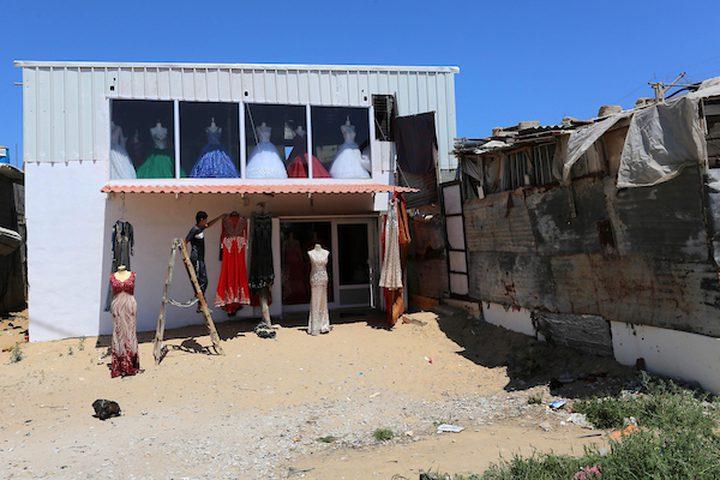 """تعمل الفلسطينية صابرين الجابري""""34عاماً"""" مع أطفالها في متجرها لتأجير وبيع فساتين الزفاف ، في خان يونس في جنوب قطاع غزة. تخرجت الجابري من قسم السكرتارية الطبية ، وفتحت متجر لاستئجار فساتين السهرة والزفاف بسبب الوضع الاقتصادي الصعب الذي تعيشه وعائلتها كما المئات من العائلات الفلسطينية في غزة."""