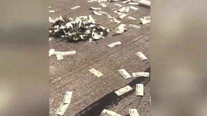 """السماء """"تمطر"""" دولارات حقيقية فوق شارع مزدحم! (فيديو)"""