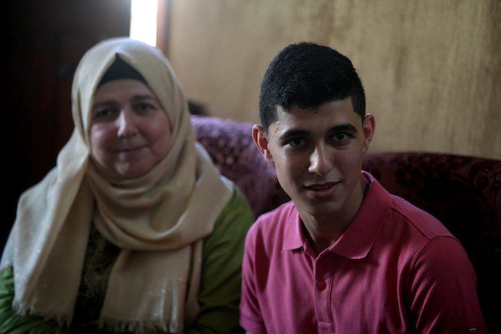 """الطالب علي مدهون ، 99.6٪ ، يحتفل مع أسرته بعد سماعه بنتائج امتحاناته النهائية"""" التوجيهي '' ، في مدينة غزة ."""