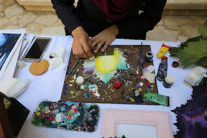 """فتاة فلسطينية تعيش في مخيم النصيرات ، وسط قطاع غزة، تعلمت الفن حتى عشقته روحها ،فرسمت العديد من الالواح الفنية التي تسلب نظر المتفرجين ،على الأوراق وأيضاً الحجارة ، فحولتها للوحات إبداعية جميلة ،لكنها فكرت بشيء مختلف ، في محاولة منها أن توصل فكرة بأن """"الابداع لا حدود له"""" .  فبحرص شديد تقوم """"لين الحاج """"21عاماً"""" بقطف أوراق العنب من حديقة منزلها ،لا لتعد منه أكلة محببة للقلوب ،ولكنها أرادت أن تغذي الأعين هذه المرة ،فتتوجه بها إلى المرسم الخاص بها لكي تحولها للوحات فنية بأناملها وفرشاتها."""