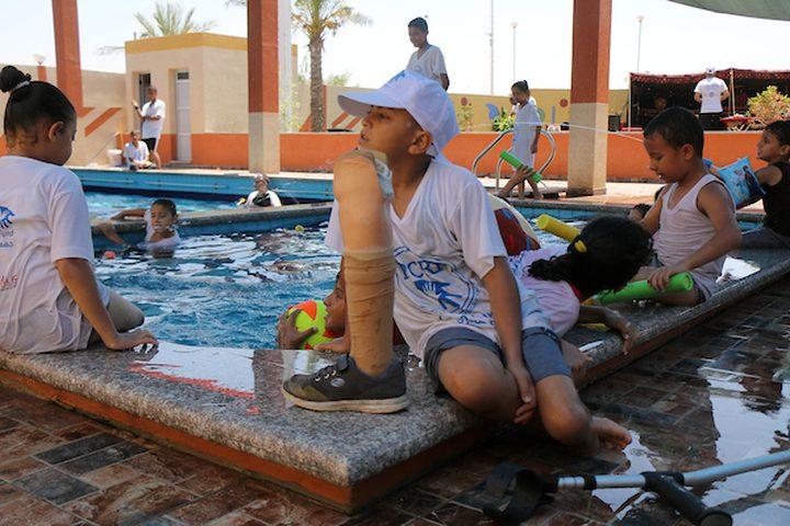 أطفال مبتورون يلعبون في حوض سباحة خلال معسكر صيفي ينظمه صندوق إغاثة الأطفال الفلسطينيين (PCRF) ، في خان يونس في جنوب قطاع غزة.