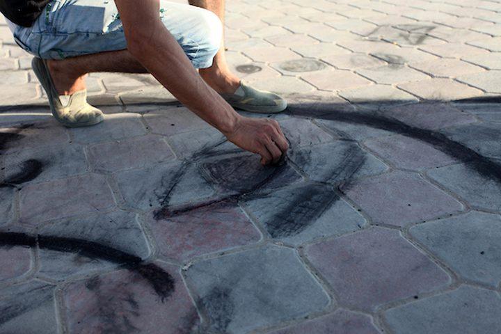 """الشاب معاوية عاشور """"24 عاماً """" ، هاوٍ للرسم ، يستخدم الفحم ليرسم ويظهر ابداعته على الأرض بالقرب من عربته التي يبيع عليها المشروبات الساخنة ، ليهرب من شبح البطالة التي تلاحقه وتلاحق الكثير من الشباب، على شاطئ بحر الشيخ عجلين،غرب مدينة غزة ."""