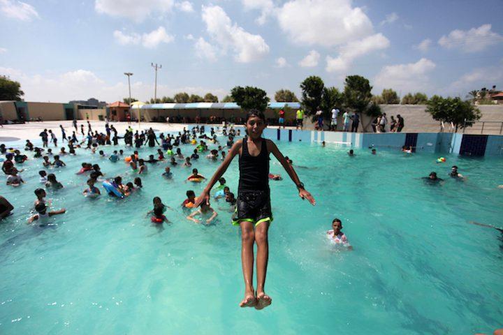 أطفال من غزة يستمتعون بالسباحة في بركة بإحدى منتجعات مدينة غزة السياحية