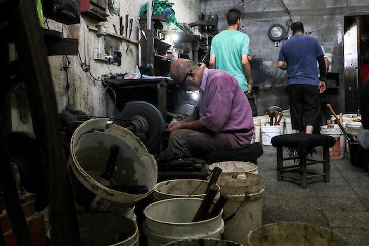 عمال في غزة، يقومون بسن السكاكين، بورشة عمل، قبيل عيد الأضحى، حيث يستخدمونها لذبح الماشية والأغنام في عيد الأضحى.