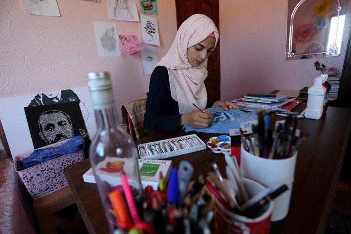 الفنانة الفلسطينية منال الاسطل 20 عاماً، ترسم على الملابس، في منزلها بخانيونس في قطاع غزة.