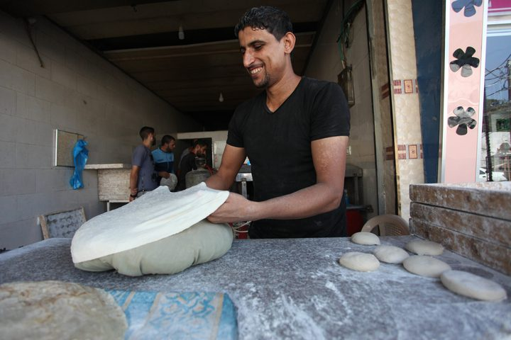 مهارة وإتقان يرقّق بكلتا يديه، قطعة عجين يتلقفها بسرعة بين كفّيه عدة مرات، ويصنع منها رغيف خبز دائري كبير.