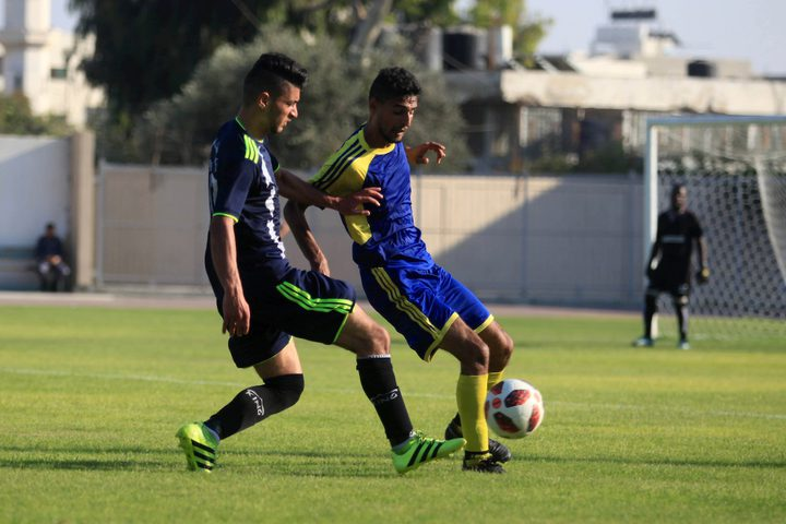 لاعبو كرة القدم من اتحاد بيت حانون والهلال يتنافسون في الدوري الممتاز على ملعب اليرموك في مدينة غزة.