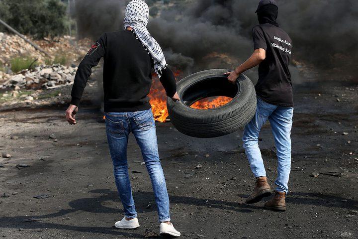 متظاهرون يحرقون الإطارات أثناء المواجهات مع قوات الاحتلال الإسرائيلي خلال مسيرةكفر قدوم السلمية الأسبوعية.