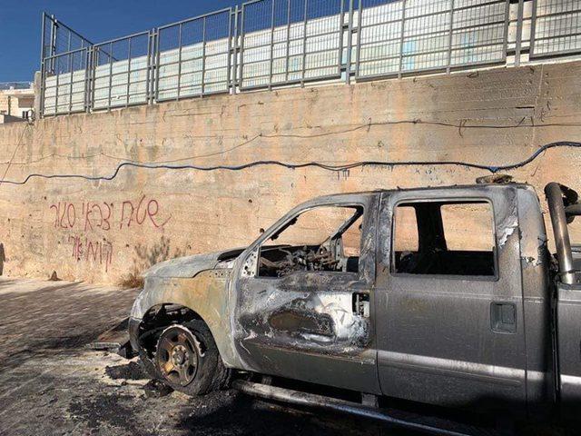 مستوطنون يحرقون مركبة ويعطبون أخريات ويخطون شعارات عنصرية